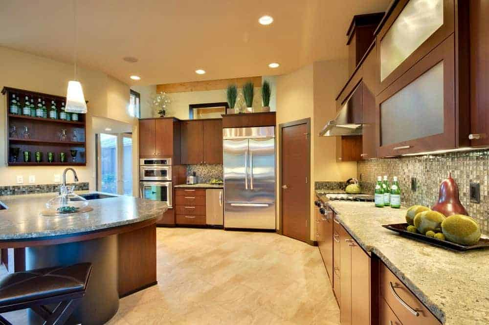 This kitchen offers stainless steel appliances and wooden cabinetry matching with the peninsula that's topped with a granite counter and sink. It has beige tiled flooring and yellow walls mounted with dark wood shelves.