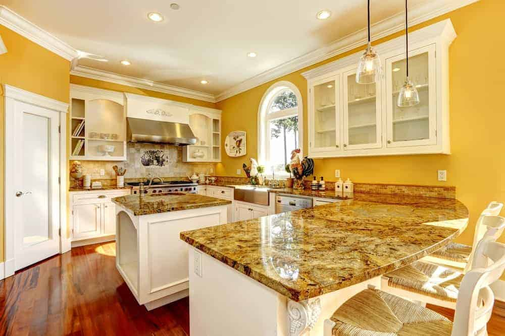This kitchen features glass front and white cabinets along with a granite top peninsula paired with wooden counter chairs. It includes an arched window and a small kitchen island that's fitted with built-in storage and sink.