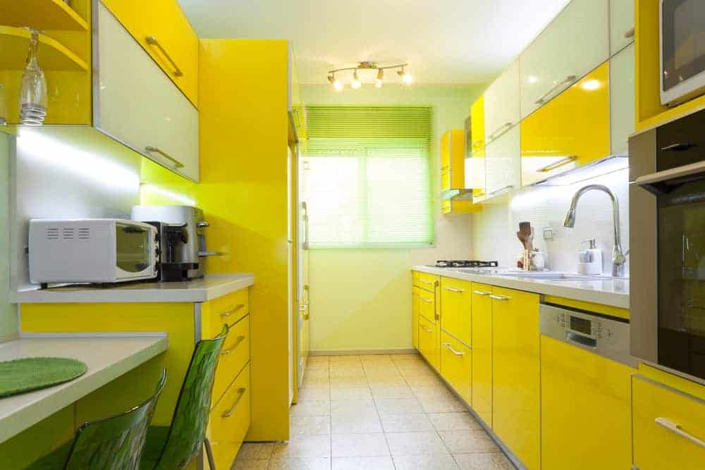 Bright kitchen with white and vibrant yellow cabinetry along with track lights mounted on the regular ceiling. There's an eating nook on the side completed with a built-in table and translucent green chairs.