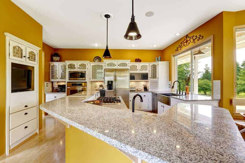 This kitchen showcases stainless steel appliances and white cabinetry against the mustard yellow walls. It includes a two-tier breakfast bar that's topped with granite counters and lighted by black dome pendants.