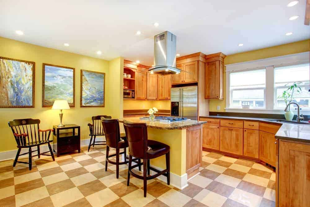 G-shape kitchen with yellow walls, wood cabinetry, and a seat-in area beside the wall with framed paintings.