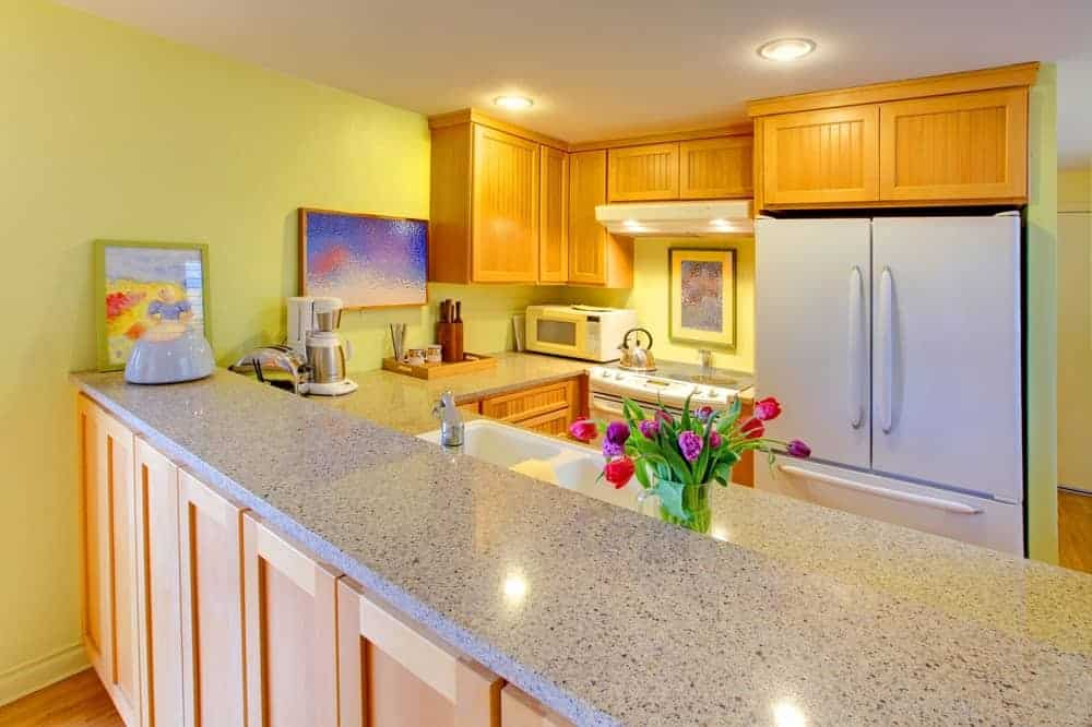 Small kitchen with white appliances and light wood cabinetry against the yellow walls. It includes lovely artworks and a raised peninsula topped with granite counters.