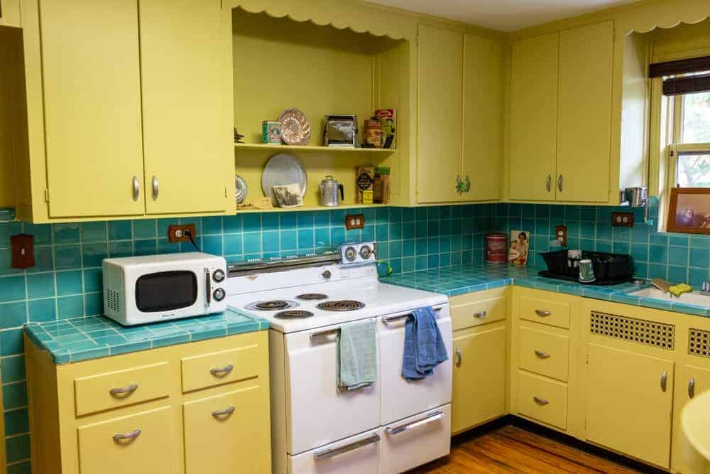 Blue backsplash tiles add a nice accent to the yellow cabinetry and white appliances in this kitchen with open shelving and natural hardwood flooring.
