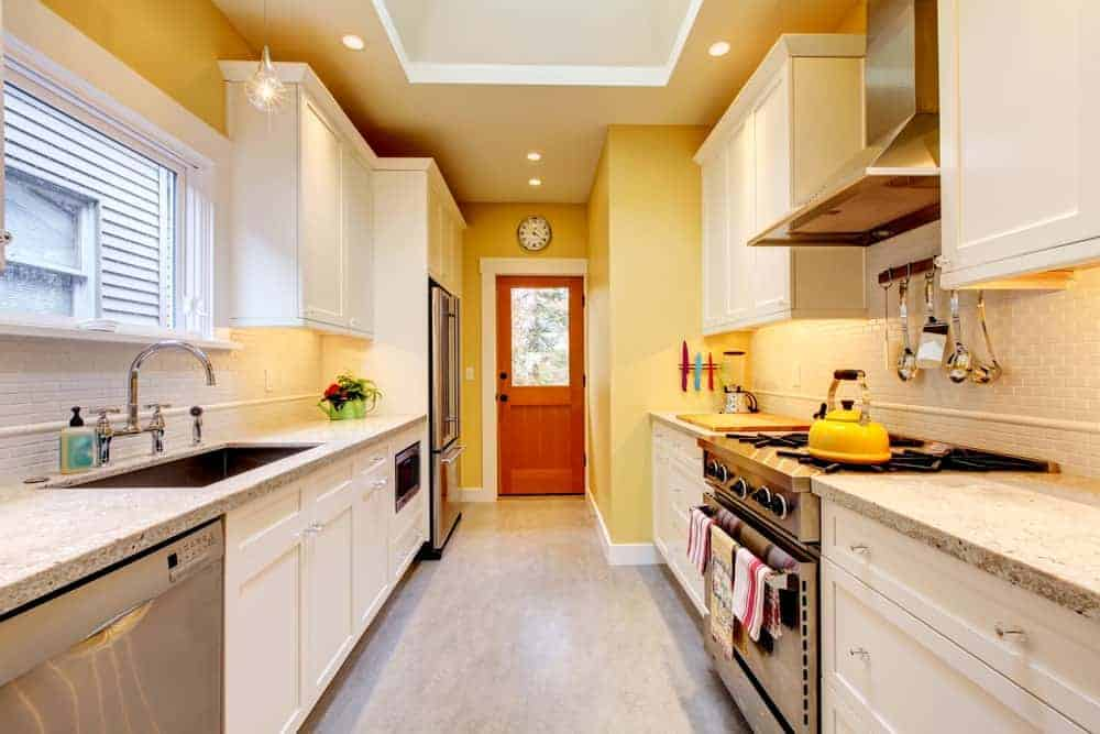 Galley kitchen boasts granite countertops and an undermount sink paired with chrome fixtures. It includes stainless steel appliances and white cabinetry lighted by a bulb pendant and recessed ceiling lights.