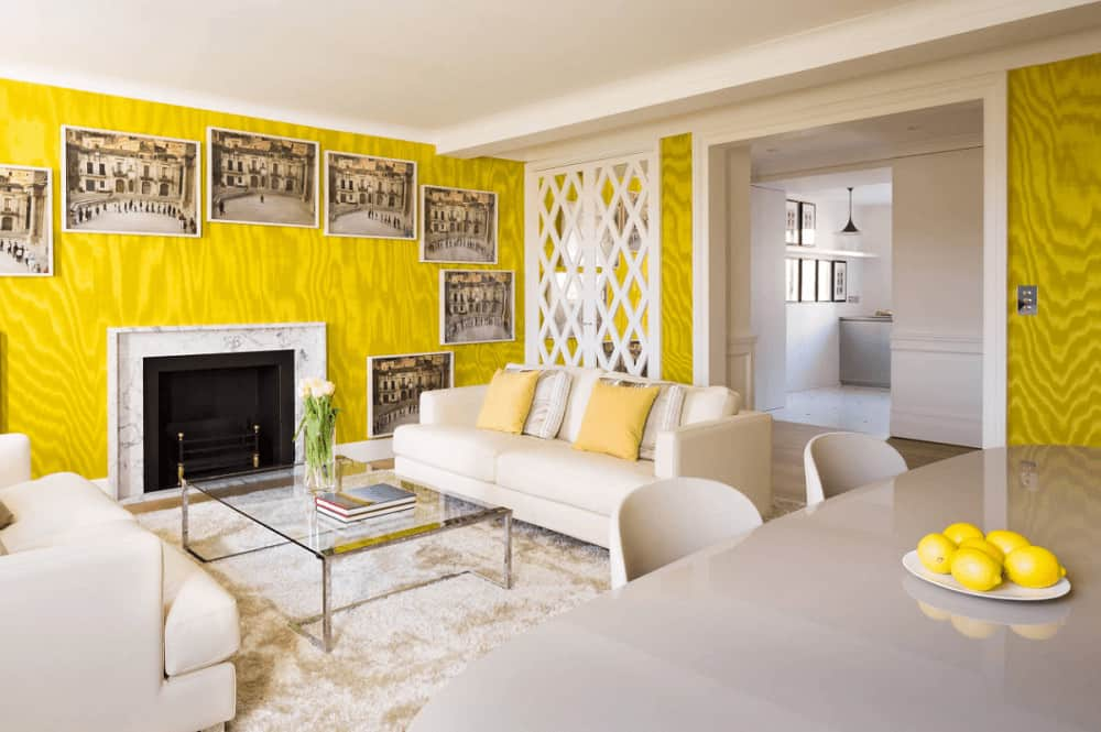 Clad in yellow wavy wallpaper, this living room boasts facing sofas and a glass top coffee table across the fireplace surrounded by framed pictures.