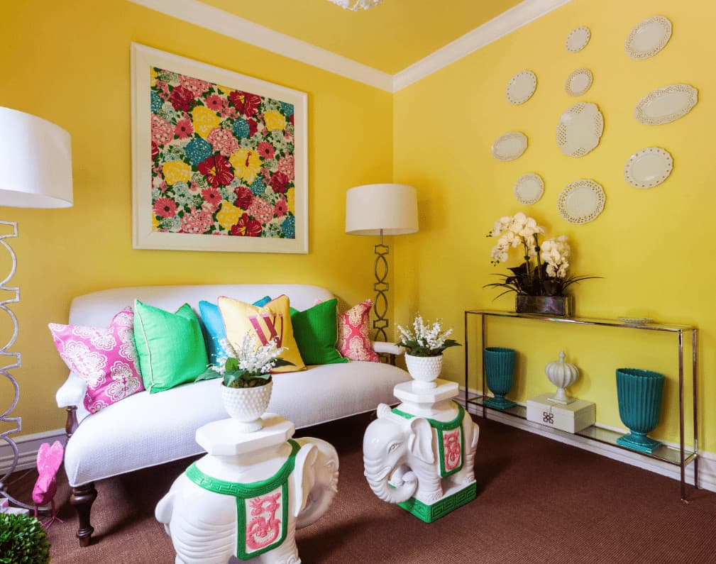 Stylish living room designed with decorative plates and a colorful floral artwork that hung above the white sofa accented with multi-colored pillows.