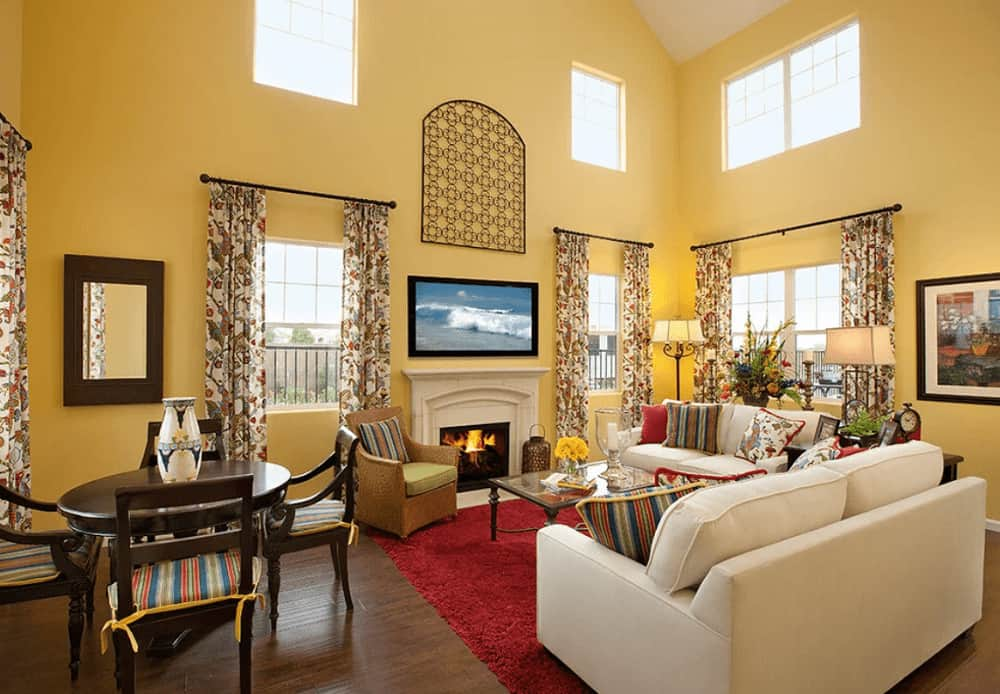 High ceiling living room with hardwood flooring and glazed windows dressed in floral draperies. It has a fireplace and white sofas paired with a glass top coffee table on a red area rug.