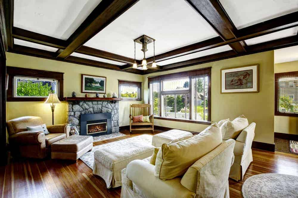 The yellow living room offers skirted seats and a leather lounge chair paired with a matching ottoman. It includes a wrought iron chandelier and a stone fireplace topped with a dark wood mantel.
