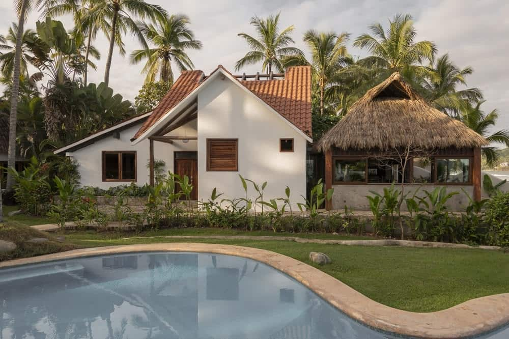 This is a full view of the tropical-style home that has bright walls, red clay tile roofs on one side and a palm hut with concrete base and bamboo frames on the other side. Thes eare then complemented by the surrounding tall tropical trees.