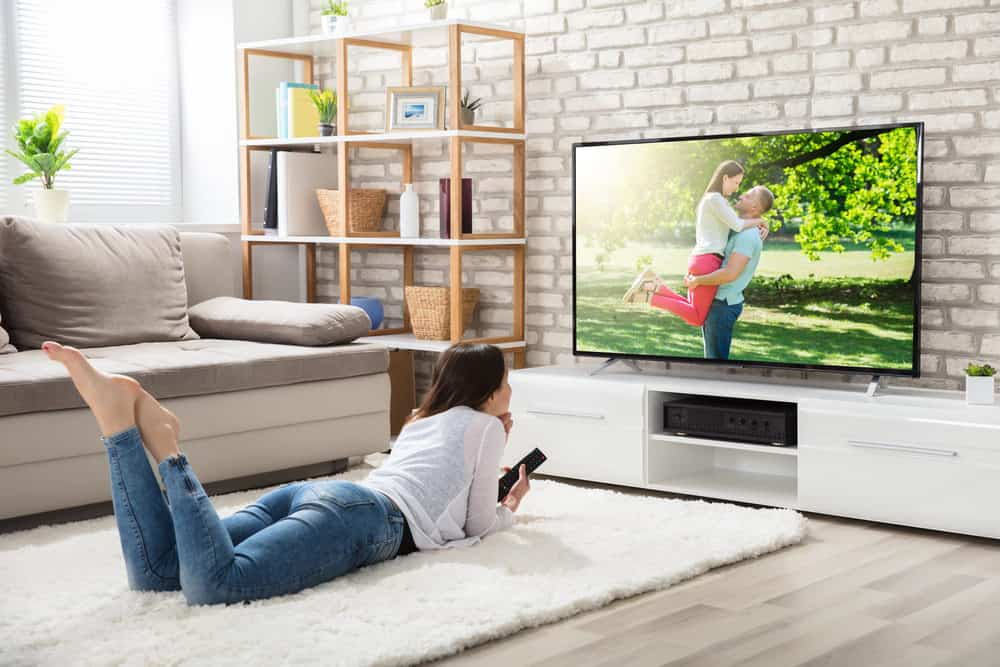 Woman watching television in living room