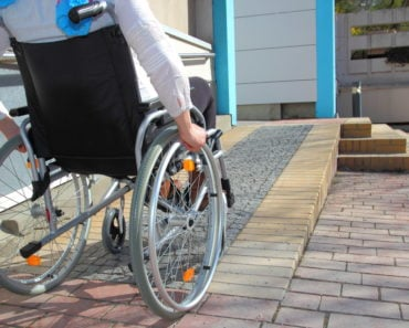 Woman in a wheelchair going up a ramp to a house