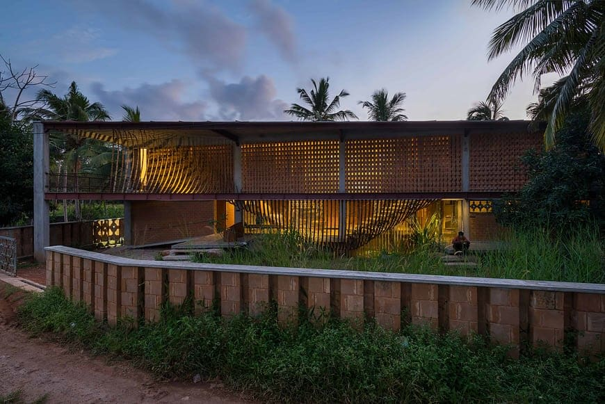 This is a nighttime view of the house exterior with slatted panels and structures in front of the house that lets through the warm glow of the interior lights fiving the house a unique and rustic look.