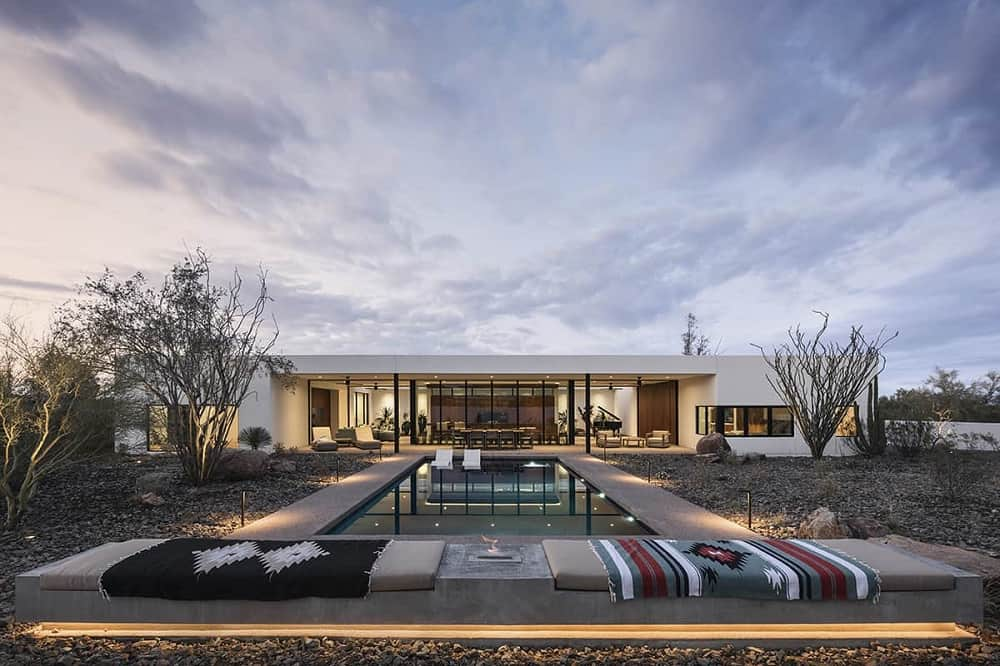 This is a view of the house from the back poolside area that has a desert landscape that complements the bright exteriors of the house with large glass walls in the middle with a warm lighting.