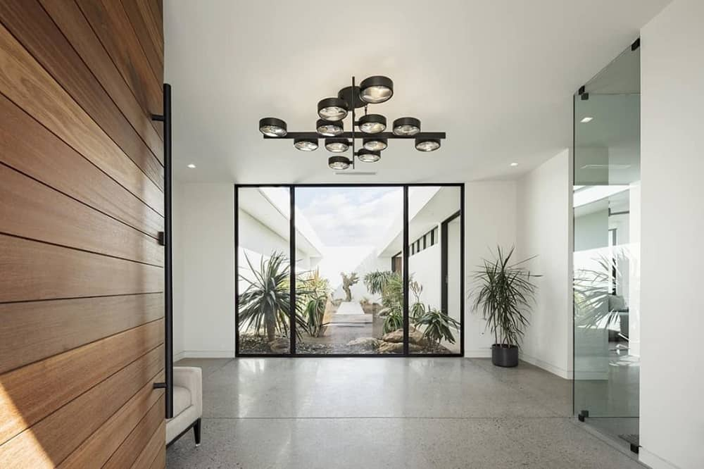 Upon entry of the main wooden door, you are welcomed by this foyer that has a modern decorative chandelier, a potted plant in the corner and a glass wall on the far side showcasing a terrarium of plants.