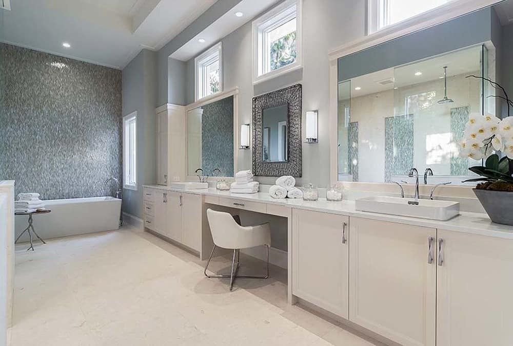 This is a spacious bathroom with a long two-sink vanity that has a beige tone to match the floor. On the far end, you can see a freestanding bathtub placed by the window.