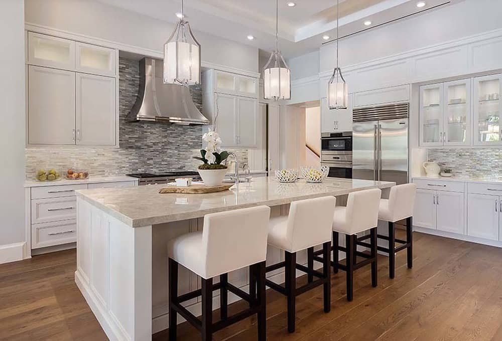 The bright white tray ceiling of this kitchen hangs lantern-like pendant lights over the beige countertop of the kitchen island that is paired with beige stools. These are all then contrasted by the dark hardwood flooring.