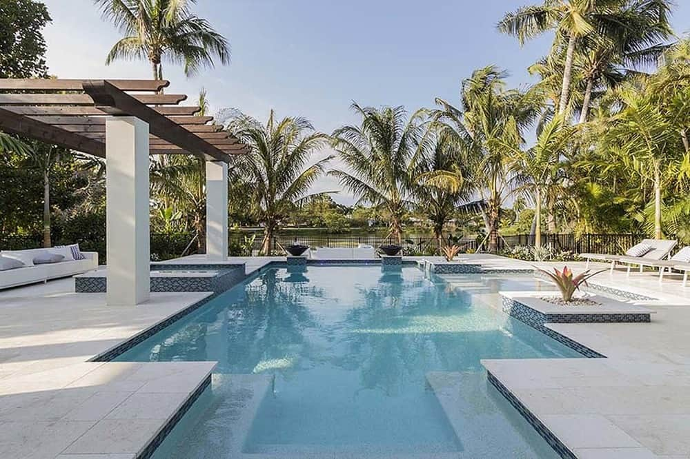 This is the back of the house that is dominated by the gorgeous pool with a cabana on the side topped with trellises. The whole backyard is surrounded by tall tropical <a class=