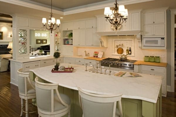 The large kitchen island has a light beige countertop paired with a couple of charming chandeliers that throw warm yellow light to complement the beige cabinetry.