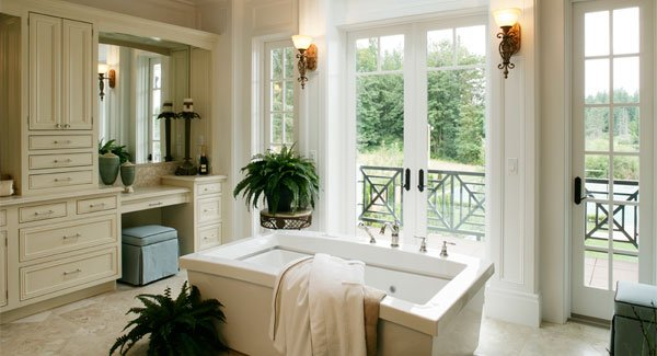 This is a classy bathroom with a large wooden structure for the vanity and a freestanding bathtub in the middle adorned with potted plants. There is also a French glass door flanked by sconces leading to the rear deck.