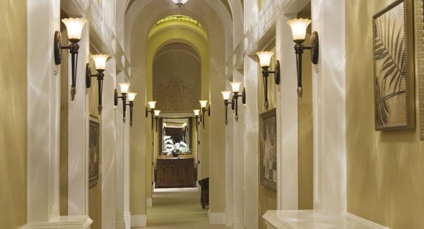 This elegant hallway foyer is framed with arches and columns that are mounted with glass sconces. On the far end is a charming wooden cabinet topped with a mirror.