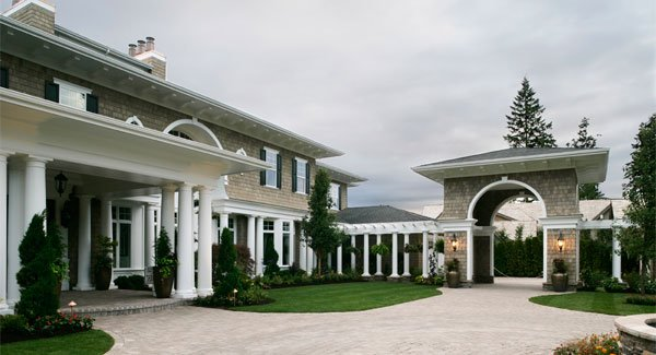 The lovely house with multiple white pillars has a covered pergola and a main gate with an open archway. These are then complemented with lawns of grass along with shrubs and trees that bring color to the exteriors.