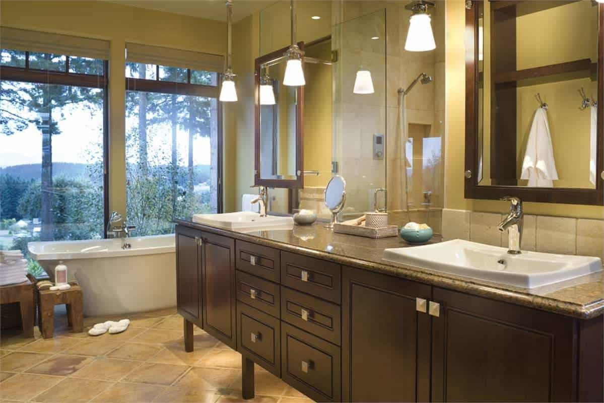 The primary bathroom is equipped with a deep soaking tub, dual sink vanity and a walk-in shower reflected in the frameless mirror in between the vanity mirrors that has matching dark brown frames to pair with the vanity.
