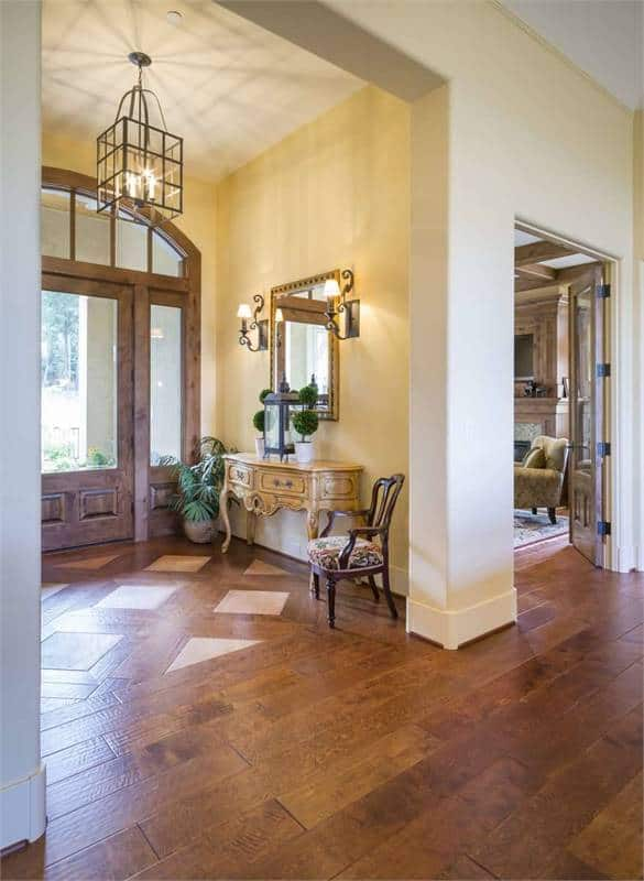 The foyer has a glazed front door, caged chandelier, and an antique console table complemented by a cushioned armchair, wall-mounted mirror and a potted plant.