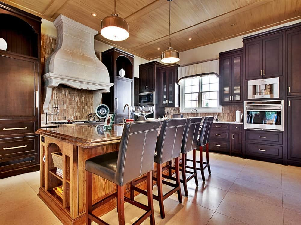 This gorgeous kitchen has lovely beige flooring tiles that complement the wooden kitchen island that is paired with brown leather stools and topped with drum pendant lights from the wood ceiling that has exposed beams.
