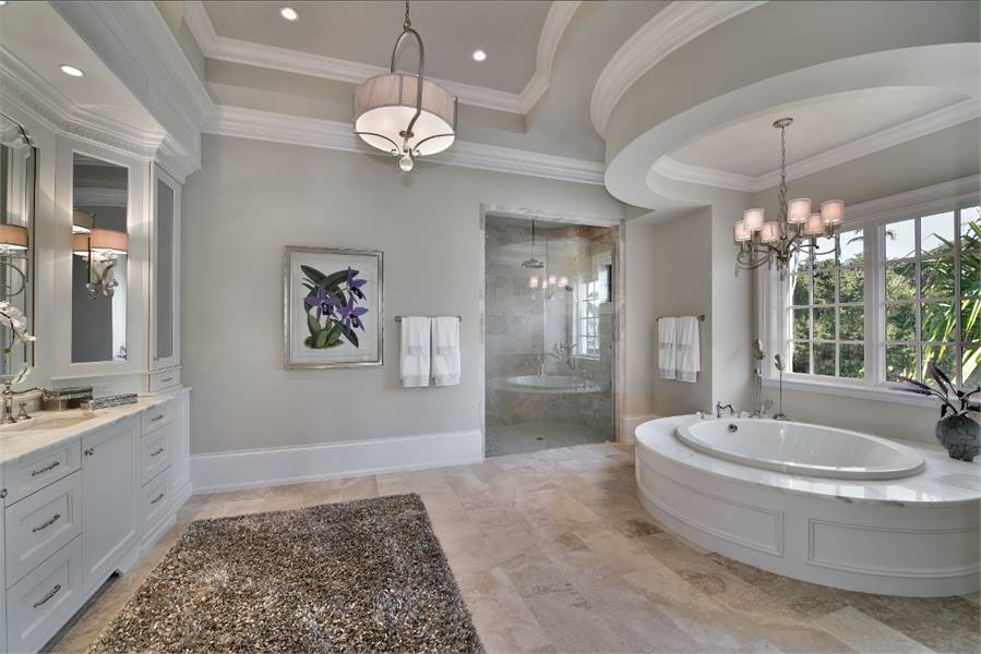 This spacious bathroom has an elliptical bathtub placed by the window and topped with a chandelier. Next to it is the glass door of the walk-in shower area.