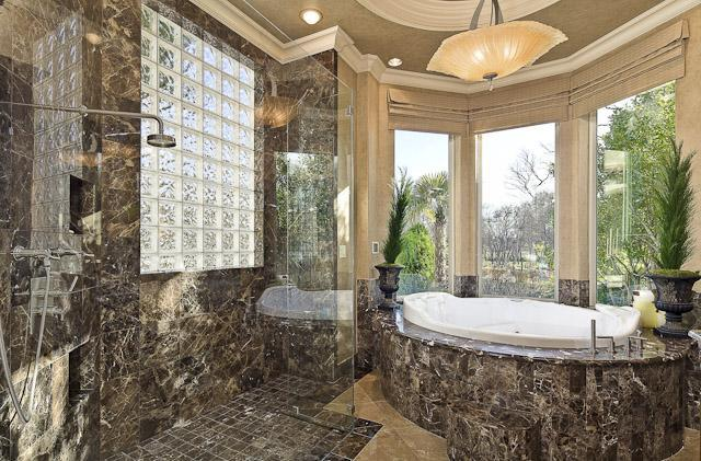 This gorgeous primary bathroom has an earthy marble tone applied to its shower area walls paired with frosted glass panels. This is also applied to the bathtub housing.
