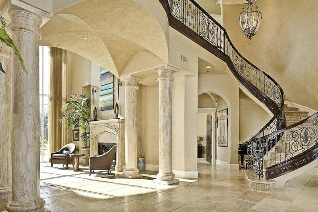 This is a grand foyer with a large winding staircase topped with a large chandelier. There is also an open archway leading to the bright living room supported by huge marble columns.