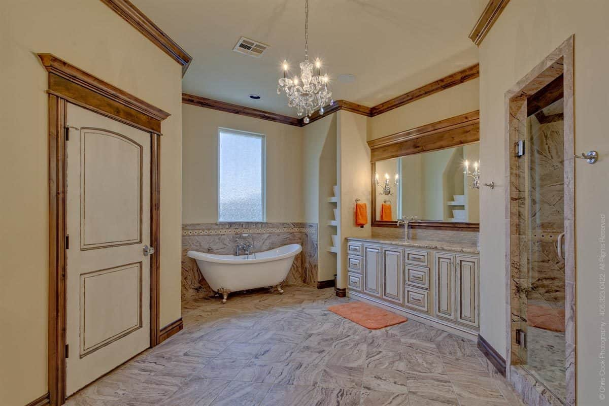This is a spacious bathroom with a charming chandelier hanging in the middle of the beige ceiling that blends with the beige walls complemented by the wooden moldings. On the the far side is a freestanding bathtub underneath the window.