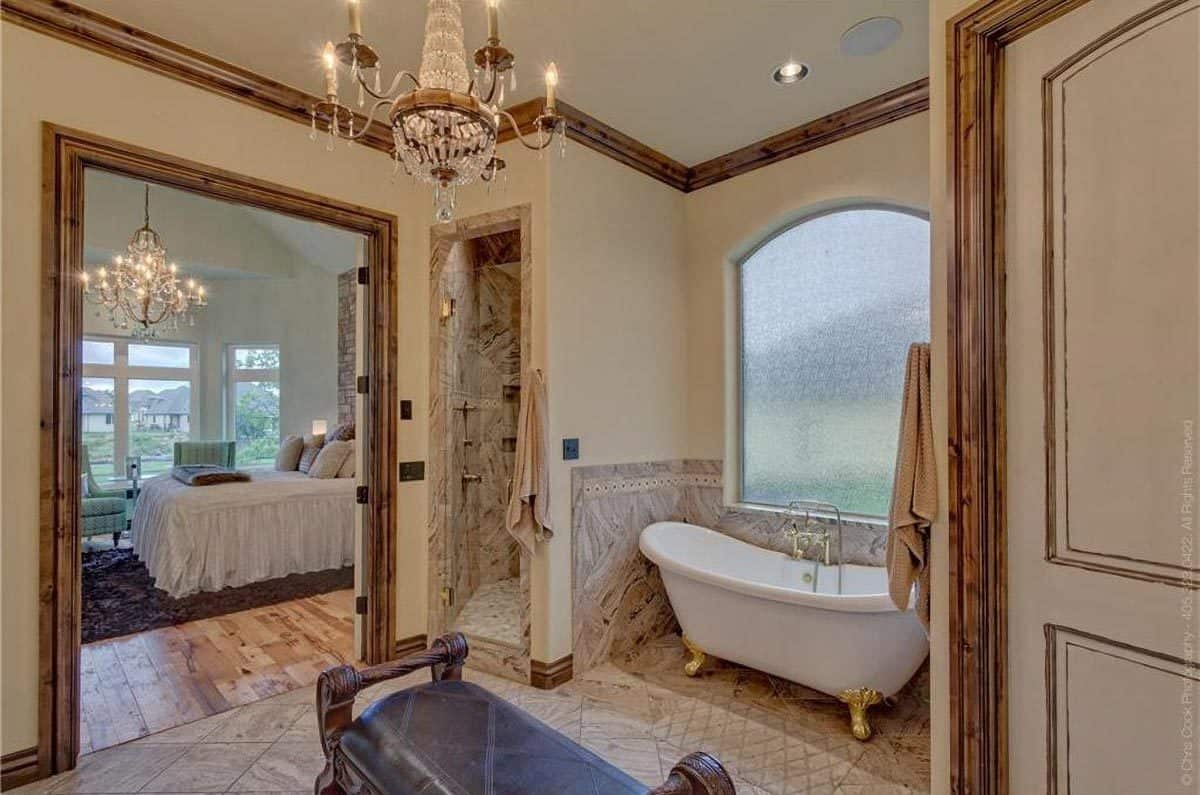 This large bathroom has a cushioned wooden bench underneath the chandelier. Across from this bench is the freestanding bathtub placed in an alcove with an arched window.