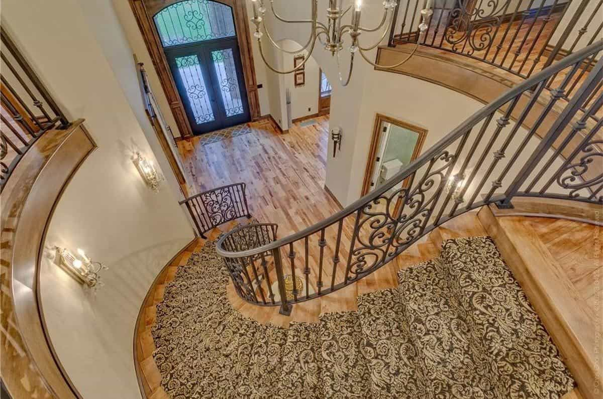 This is a view of the foyer from the vantage of the second level landing. Here you can see the beautiful main doors dominated by glass panels and wrought iron intricate patterns. The foyer has a simple hardwood flooring topped with a majestic chandelier.