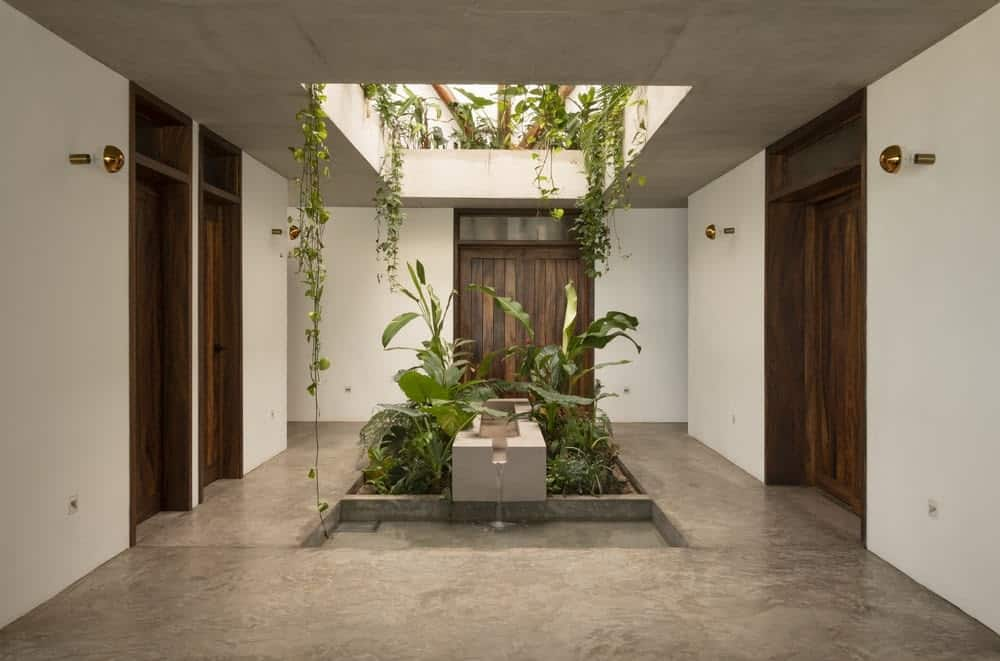 Upon entry into the house, you are welcomed by this foyer that has an open ceiling with creeping vines and a miniature garden with fountain in the middle.