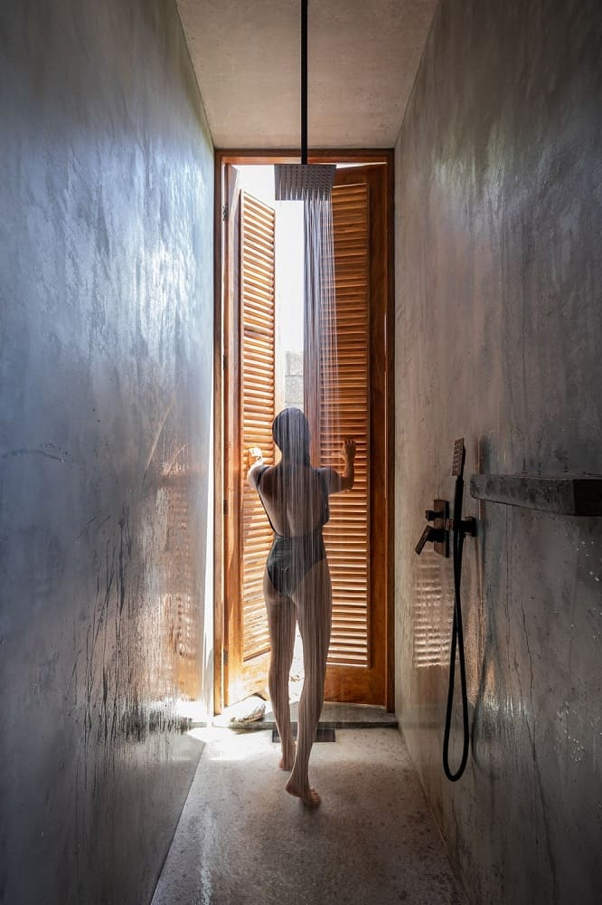This is a tall and thin tropical-style bathroom with concrete walls and a concrete floor that make the stainless steel fixtures and tall shuttered window stand out.
