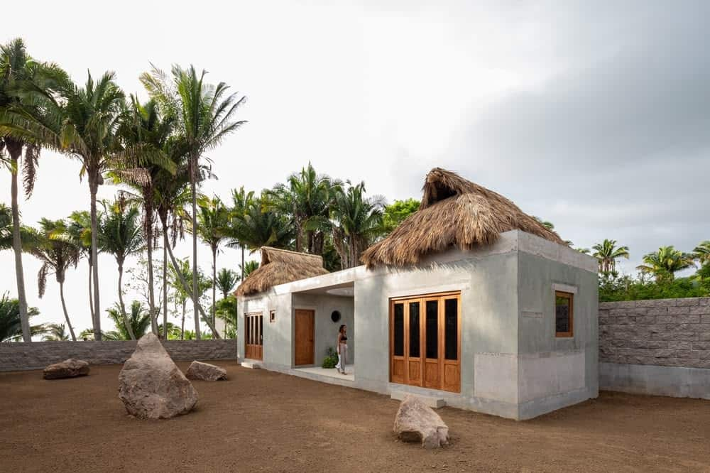 This is a view of the house exterior that has concrete exterior structures with wooden windows and doors that fold open topped with palm leaf roofs giving it a rustic tropical look.