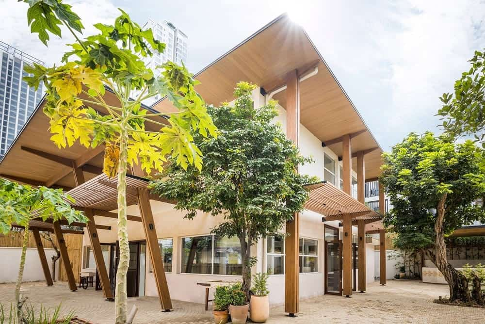 This is an exterior view of the house with bright beige exterior walls and multiple windows. These are then complemented by the large wooden structures and panels attached to it as well as the trees and shrubs of the landscaping.