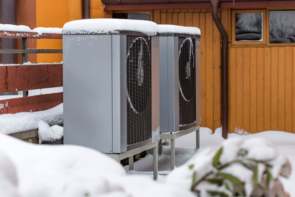Modern heat pumps outside a home and covered in snow.