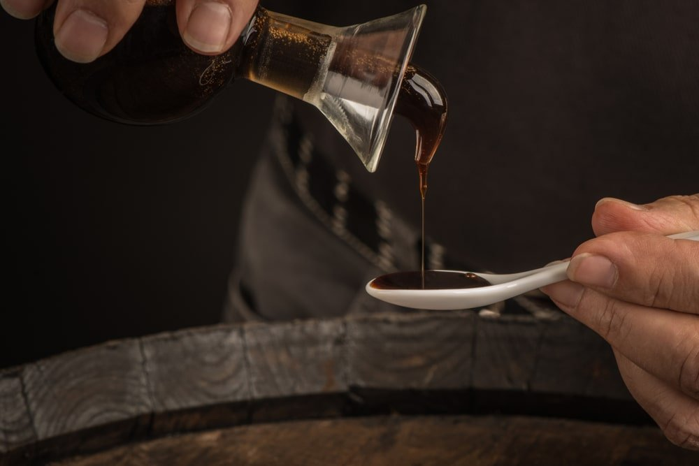 Balsamic vinegar poured on a spoon.