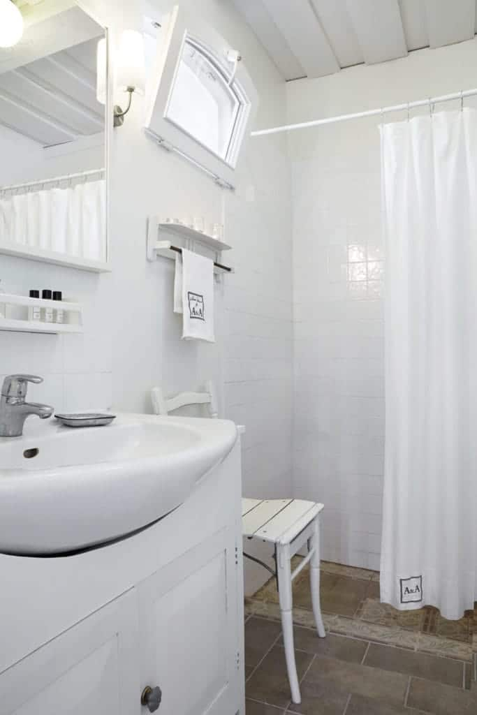 Concrete tiled flooring stands out against the white walls and furnishings in this shabby-chic style bathroom with a pedestal sink and a small shower area enclosed in a grommet curtain.