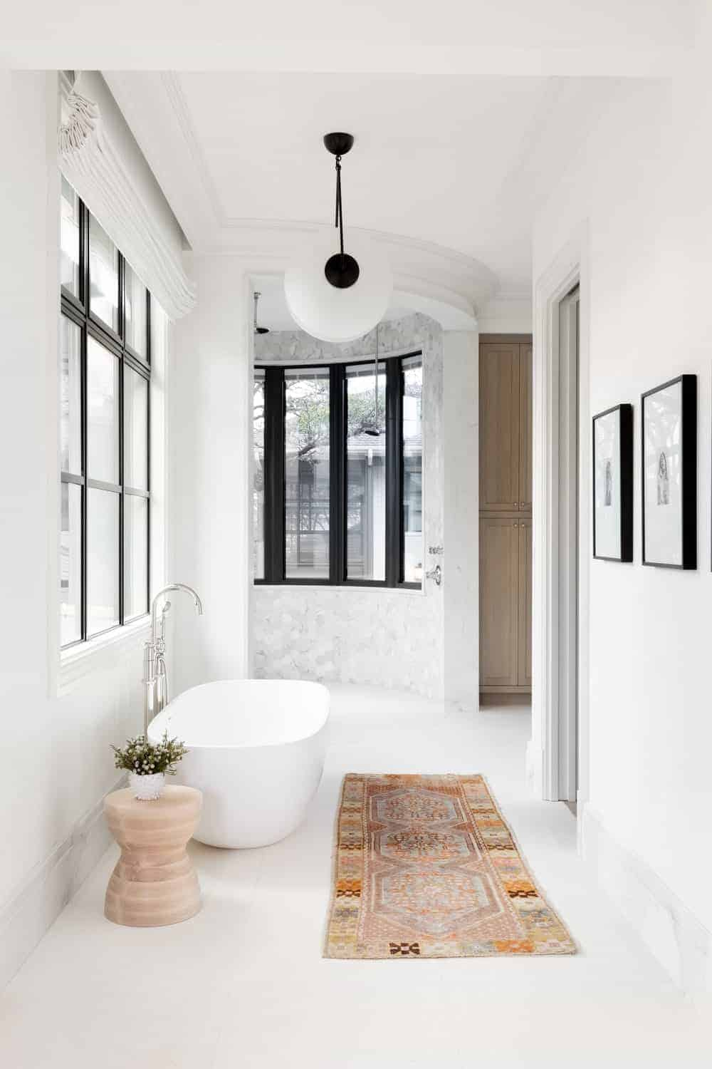 A printer runner stands out against the white floor and walls mounted with black framed artworks. It is accompanied by a round side table and a freestanding bathtub with chrome fixtures.