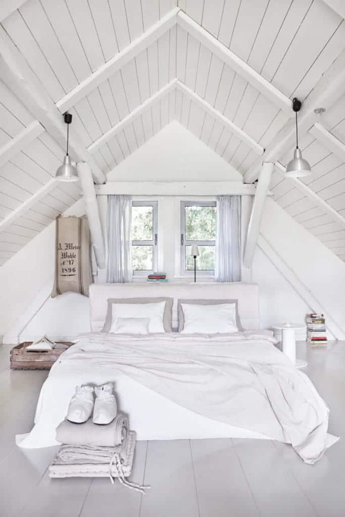 An all-white bedroom illuminated by chrome dome pendants along with natural light from the glazed windows that are covered in sheer curtains. It has a comfy bed and a round bedside table over wide plank flooring.