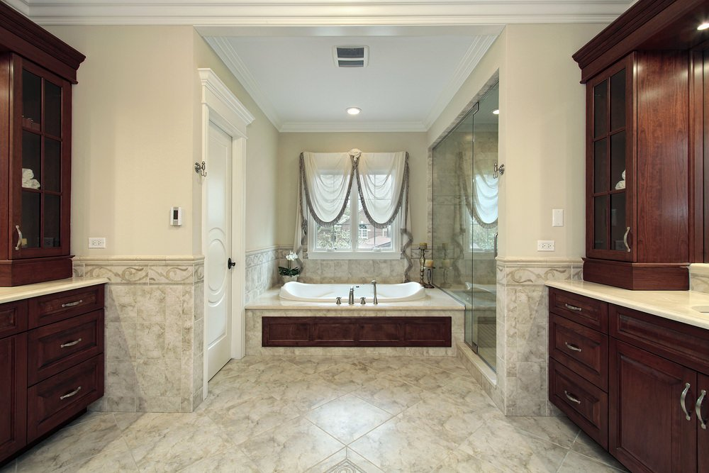 A spacious primary bathroom featuring stylish tiles flooring. The room has two sink counters, a drop-in soaking tub, a toilet room and a walk-in shower room.