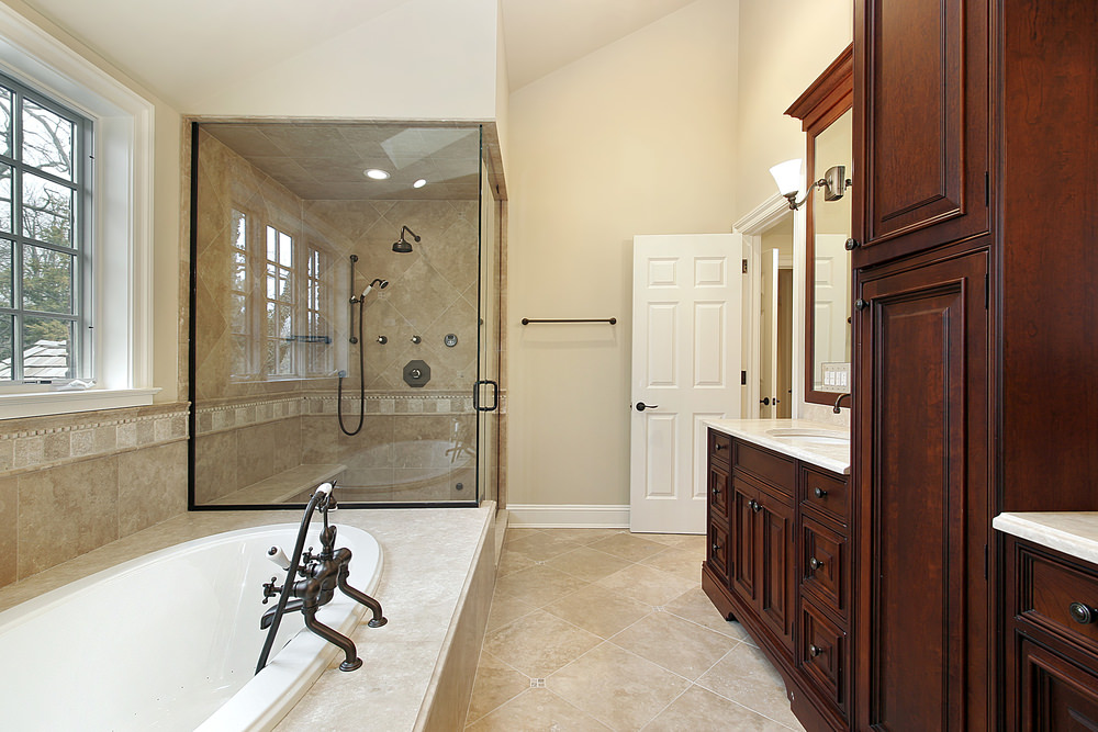 Primary bathroom with a walk-in shower room and a drop-in soaking tub. The room has a tall ceiling and beige tiles flooring.