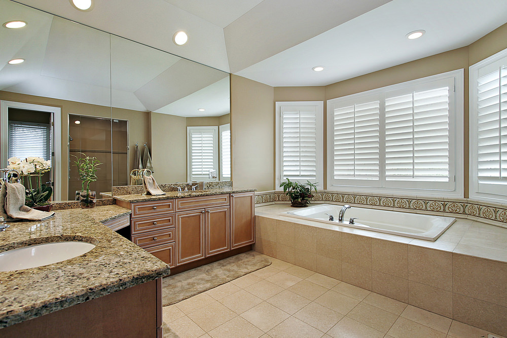 A spacious primary bathroom featuring a white ceiling and beige tiles floors. The room has two sink counters with granite countertops. There's a walk-in shower and a drop-in tub by the windows.