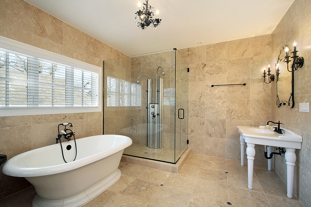 Primary bathroom with a walk-in shower and a freestanding tub, surrounded by beige tiles walls and floors.