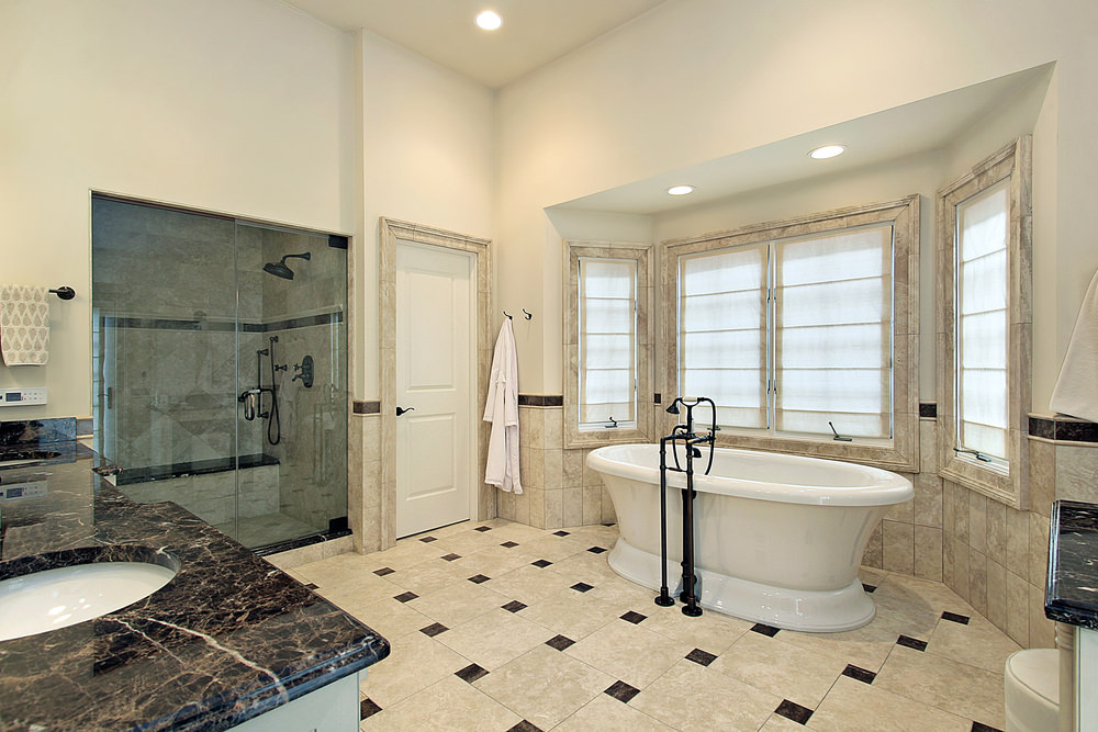 This primary bathroom features stylish tiles flooring. It also offers a walk-in shower, a freestanding tub and a black marble sink counter with two sinks.