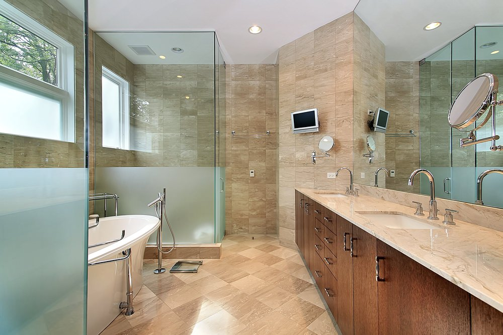 This primary bathroom offers a walk-in shower, a long marble sink counter with two sinks, a freestanding deep soaking tub and a small TV on the wall. The room features stylish beige tiles walls and floors.
