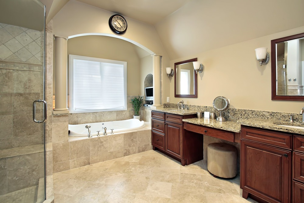 Primary bathroom featuring beige tiles flooring, a drop-in tub, a walk-in shower, a pair of sinks and a powder desk in between, all featuring granite countertops.